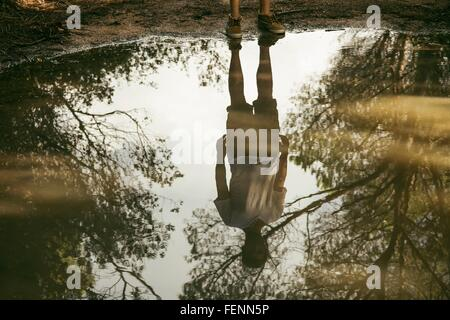 Full length reflection of young man in puddle, Costa Smeralda, Sardinia, Italy - Stock Photo