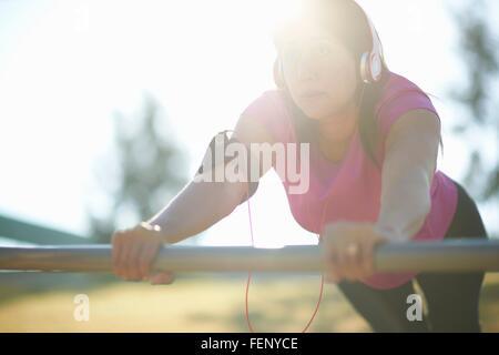 Mature woman wearing headphones doing push up using metal bar - Stock Photo