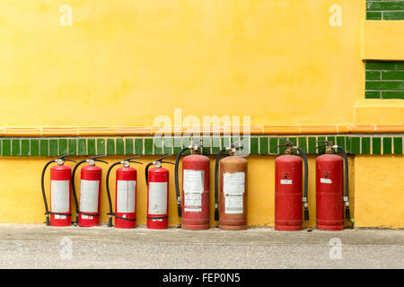Row of fire extinguishers against a wall in Hanoi, Vietnam - Stock Photo