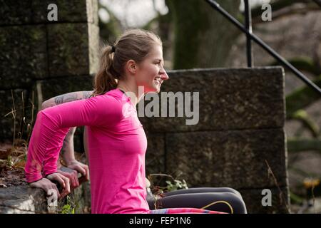 Couple, hands behind back doing push ups on stone steps, looking away smiling - Stock Photo