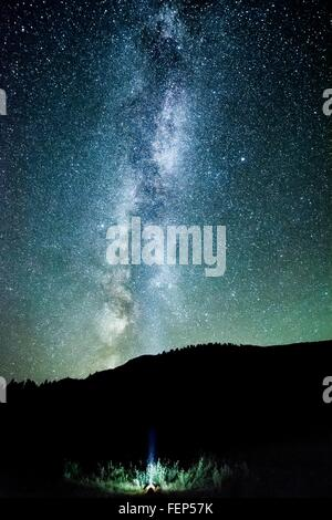 Man looking up at night sky and milky way from mountain forest, Penticton, British Columbia, Canada - Stock Photo