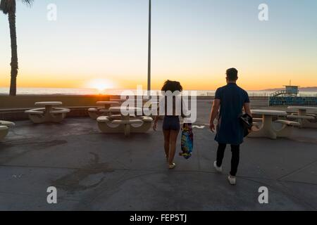 Couple walking near beach, holding skateboards, rear view - Stock Photo
