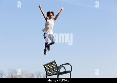 Young woman jumping off park bench - Stock Photo