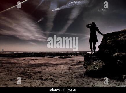 Silhouette Woman On Rock By Sea Against Sky At Dusk - Stock Photo