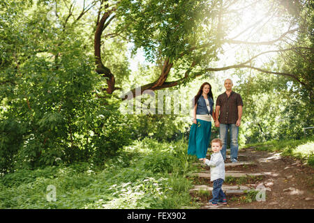 Happy Family Having Fun Outdoors. Pregnant Woman, Man and Cute Little Boy. Natural Colors. Selective Focus on a - Stock Photo