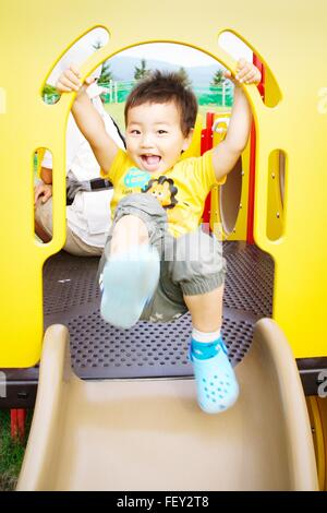 Portrait Of Cheerful Boy On Playground Slide - Stock Photo