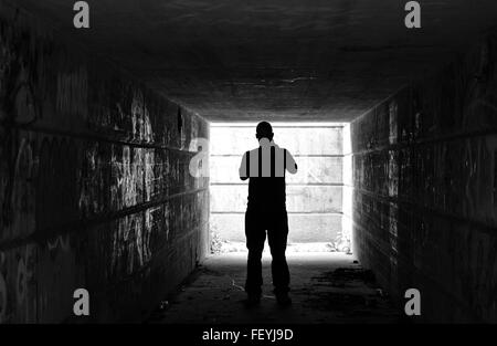 Silhouette Man Standing In Dark Tunnel - Stock Photo
