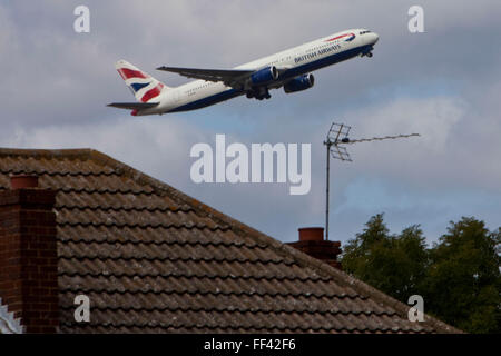 A British Airways Boeing 777 taking off from London Heathrow, south runway close to local houses in Hatton. - Stock Photo