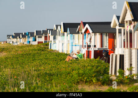 Woman sitting on sun lounger and reading newspaper at colorful wooden changing houses on the beach of Skanör in - Stock Photo