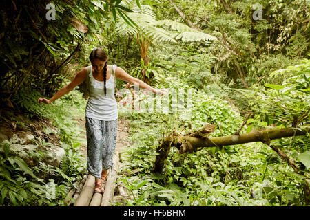 A woman walking carefully across a bamboo bridge in the jungle. - Stock Photo