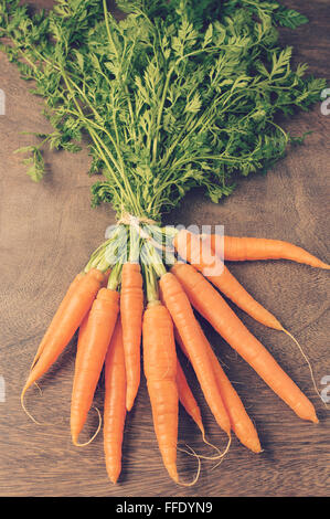 A bunch of fresh carrots on dark brown wooden table - Stock Photo
