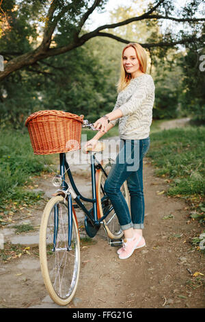 Young Happy Woman on Vintage Bicycle with Basket in Park at the Sunset. Full Height, Neutral Colors. - Stock Photo