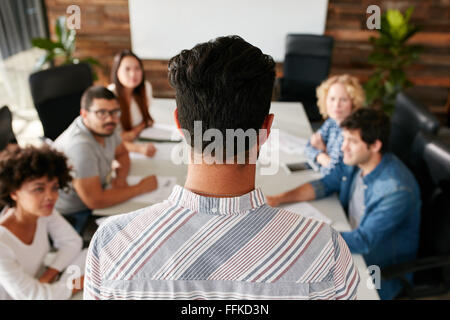 Rear view portrait of man giving business presentation to colleagues in conference room.  Young people meeting in - Stock Photo