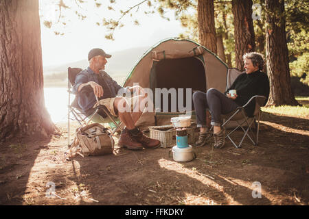 Portrait of happy senior couple sitting in chairs by tent at campsite. Mature man and woman relaxing and talking - Stockfoto