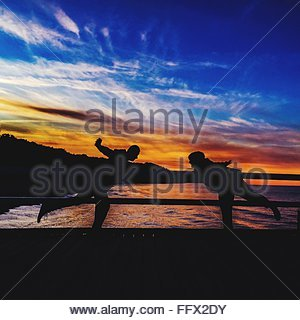 Silhouette Of Couple Balancing Against Dramatic Sky During Sunset - Stock Photo