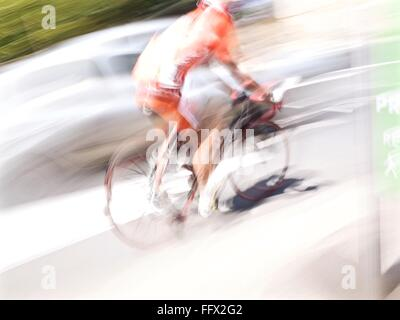 Blurred Motion Of Man Riding Bicycle On Road During Sunny Day - Stock Photo