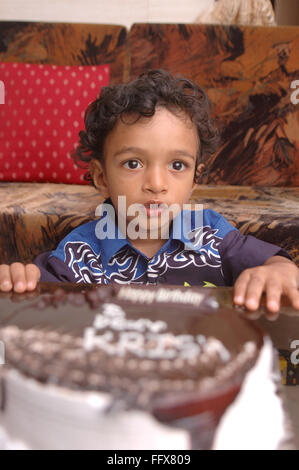 South Asian Indian small boy of 3 years sitting in front of his birthday cake MR#468 - Stock Photo