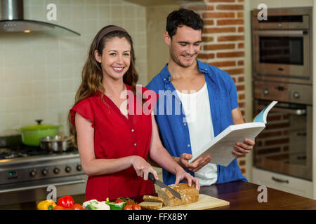 Portrait of woman cutting loaf of bread and man checking recipe book - Stock Photo