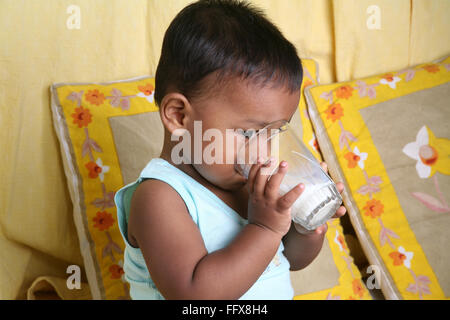 South Asian Indian small boy of 1 year drinking milk by his own MR#642 - Stock Photo