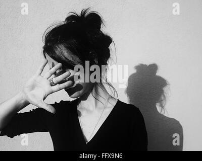 Young Woman Protecting Face From Sunlight - Stock Photo