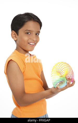 Ten year old boy playing with colourful magic spring MR#703V - Stock Photo