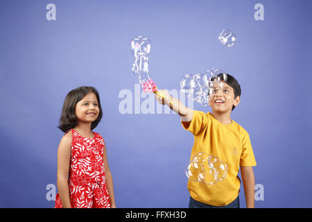 Ten old boy creating soap bubbles and eight year old girl looking at him MR#703U,703V - Stock Photo
