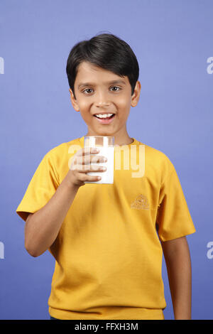 Ten year old boy holing glass of milk MR#703V - Stock Photo