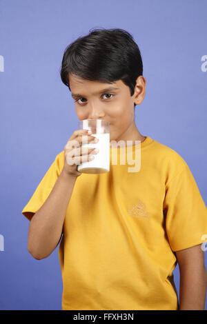 Ten year old boy holing glass of milk and drinking from it MR#703V - Stock Photo