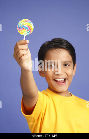 Ten year old boy showing lollipop MR#703V - Stock Photo