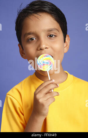 Ten year old boy holding large colourful lollipop licking MR#703V - Stock Photo