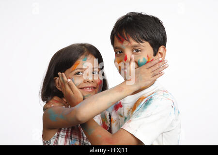 Ten and eight year old boy and girl applying colours on each other cheek on Holi festival MR#703U,703V - Stock Photo