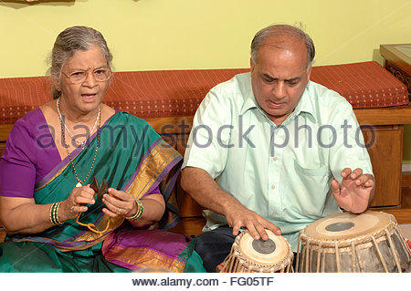 Indian Hindu old lady singing bhajan and man playing musical instruments in house , Bombay Mumbai , Maharashtra - Stock Photo