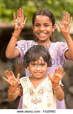 Ten and six year old girls showing mehendi design on both hand palms in Salunkwadi , Ambajogai , Maharashtra , India - Stock Photo
