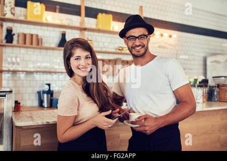 Portrait of happy young couple at cafe with a cup of coffee and digital tablet. Caucasian couple standing together - Stock Photo