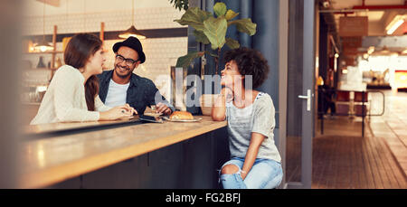 Portrait of three young people sitting together at a cafe. Group of young friends meeting in a coffee shop. - Stock Photo