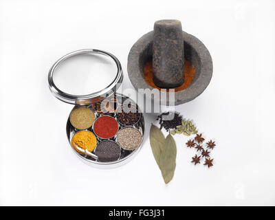 Different types of spices in bowls in stainless steel box with old stone grinder - Stock Photo