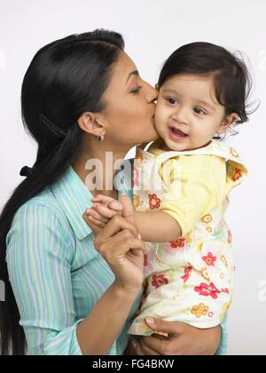 Indian mother kissing on cheek of baby girl MR#702O,702L - Stock Photo