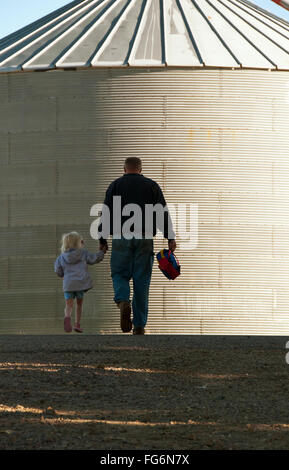 Agriculture - A farmer and his young daughter walk hand-in-hand through his farm yard with a grain bin in the background - Stock Photo