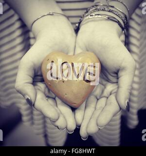 Cropped Image Of Woman Holding Heart Shape Stone With Text - Stock Photo