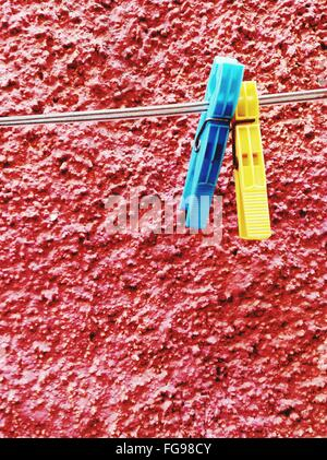 Close-Up Of Clothespin Hanging On String Against Red Wall - Stock Photo