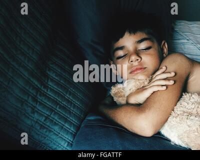 High Angle View Of Boy Sleeping With Stuffed Toy On Bed At Home - Stock Photo