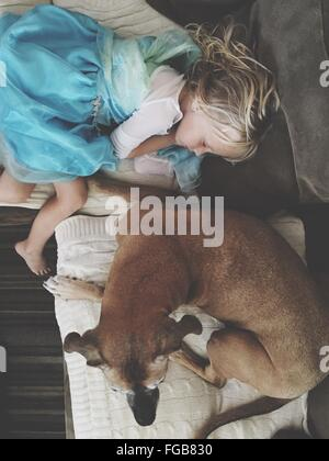 High Angle View Of Girl Sleeping On Sofa By Dog At Home - Stock Photo