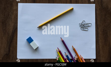 High Angle View Of Colored Pencils With Eraser And Paper Clips On Paper - Stock Photo