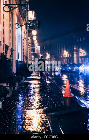 Rear View Of Man Walking On Wet Footpath In City At Night - Stock Photo