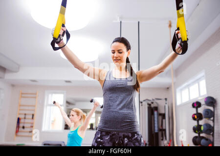 Woman in gym training arms with trx fitness strips - Stock Photo
