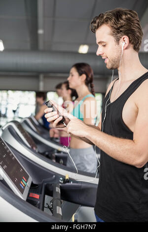 Smiling muscular man on treadmill listening to music - Stockfoto
