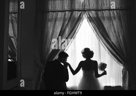 bride and groom standing in front of window - Stock Photo