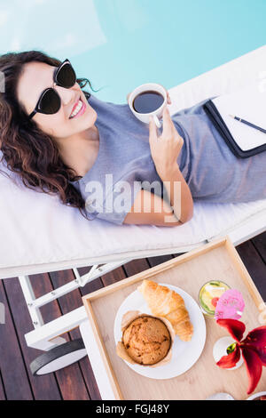 Young woman having cup of tea near poolside - Stock Photo