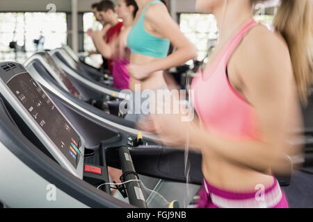 Fit woman running on the treadmill while listening music - Stockfoto