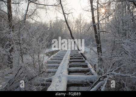 Old broken wooden pedestrian bridge covered with snow in winter - Stock Photo